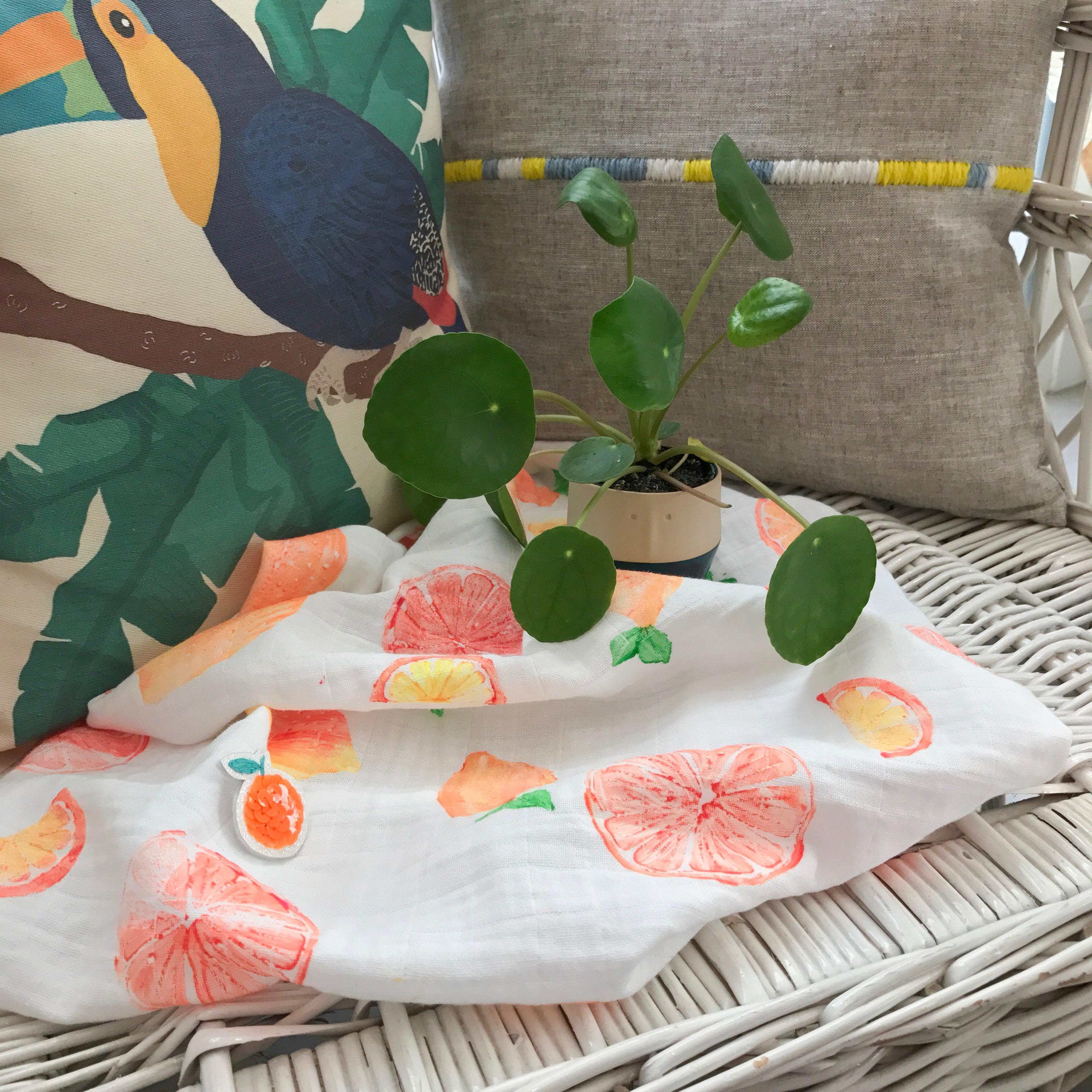 lange pour bébé avec des oranges, une broche Parisi et un pilea